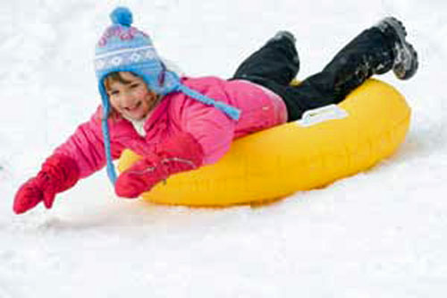Photo of child sliding down snow hill on inner tube