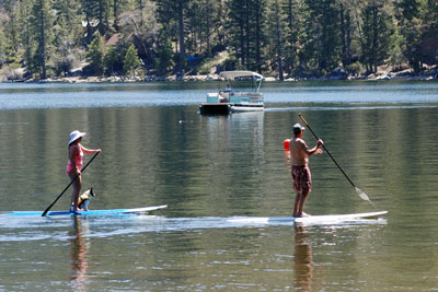 Photo of two people and their dog on paddleboards at Pinecrest Lake, CA